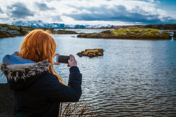 Girl With Red Hair Takes Smart Phone Photo at Lake Thingvellir in Iceland on Winter Vacation