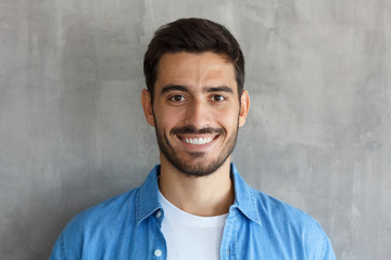 Indoor photo of handsome European guy pictured isolated on grey background standing close to camera with dark face hair and short haircut, looking satisfied and happy, spending his leisure time