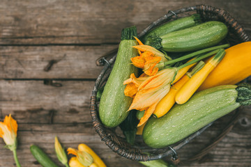 Freshly picked zucchini in a basket on a wooden table. Harvest season. Top view, selective focus.