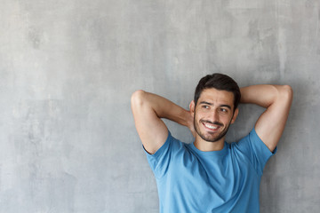 Indoor shot of handsome European guy pictured isolated against grey textured wall leaning to it in casual clothes, head resting on risen arms, looking relaxed and completely satisfied with life