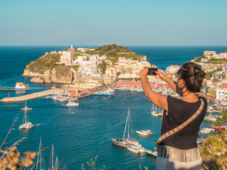 Happy young woman tourist taking smartphone pictures of town on Ponza island in Italy traditional sea city landscape.