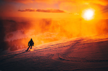 Man ski in ski resort. Winter sport photo. Orange sunset light in background. Edit space. Christmas and New Year time, snowy photo, edit space