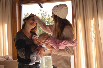 Lesbian couple holding their babies