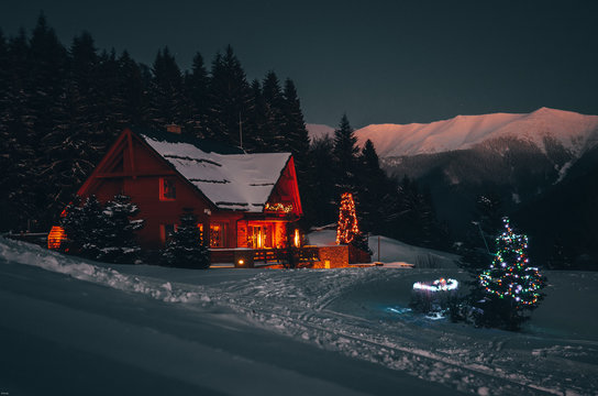 Christmas cottage in dark winter night in mountains
