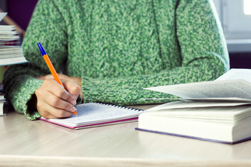 close up  woman in  green sweater holding pen,  table with  notebook and  book