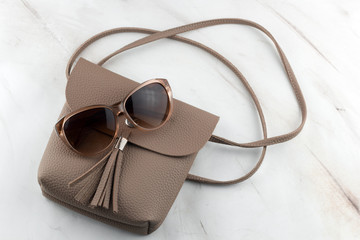 fashionable women's luxury brown bag and sunglasses top view on marble background