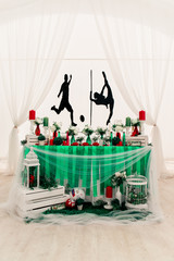Soccer and pole sport dancer wedding decor in Eco rustic style with green ribbons, red candles, bottles, white flowers and green leaves.