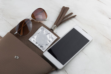 top view contents of women  bag  condom,phone  and sunglasses in an open bag on the marble table