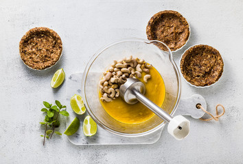 Preparation of vegan paleo cream from cashew nuts and mango puree for mini tarts made of nuts and dates. healthy alternate raw food with hand blender