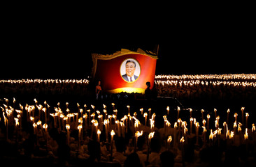 Participants ride with a portrait of Kim Il Sung during a torchlight procession during the celebration marking the 70th anniversary of North Korea's foundation in Pyongyang