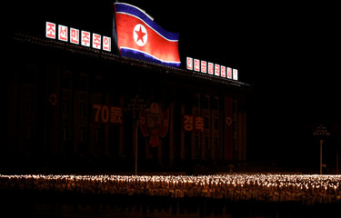 Participants shout slogans as they carry torches during a torchlight procession during the celebration marking the 70th anniversary of North Korea's foundation in Pyongyang