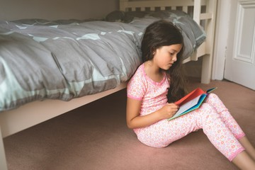 Girl reading book in bedroom