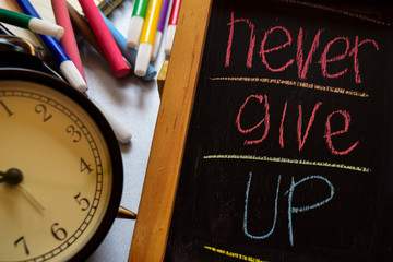 Never give up on phrase colorful handwritten on chalkboard, alarm clock with motivation and education concepts