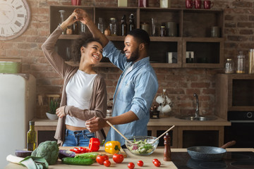 Happy romantic couple dancing in kitchen while cooking