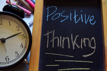 Positive thinking on phrase colorful handwritten on chalkboard, alarm clock with motivation and education concepts
