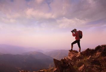 Young woman hiker taking photo on mountain peak