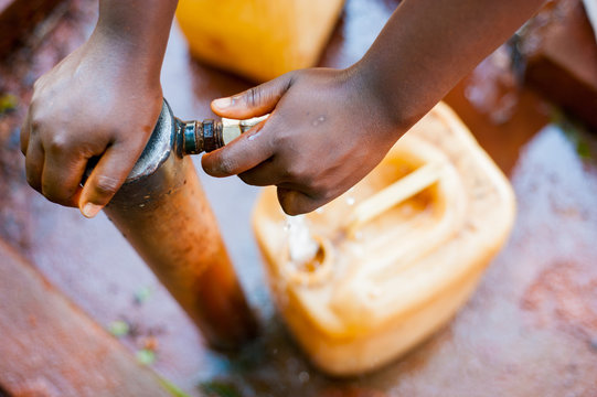 above close view up of young african child hand filling tank with tap water with green background
