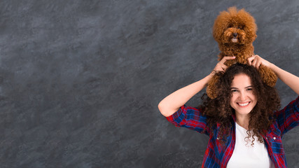 Woman lifting up her poodle dog up over her head