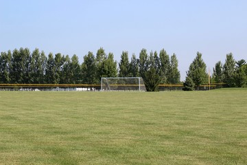 The soccer goal on the playing field of a summertime day.