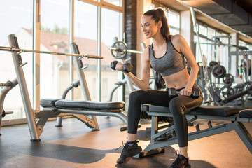 Fitness girl exercsing with weights at gym