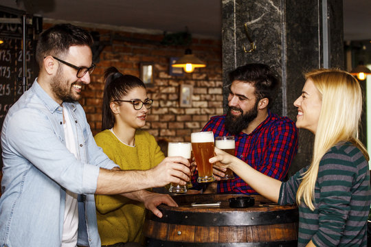 Group of four people toasting with glasses full of beer in local pub
