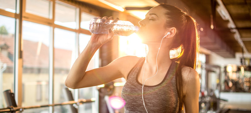 Side view panoramic profile of beautiful sporty girl with headphones drinking water during morning workout at gym