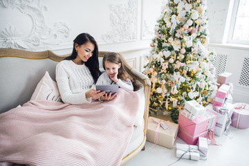 Portrait of smiling little daughter sitting together with her mother and using digital tablet at home at christmas time.