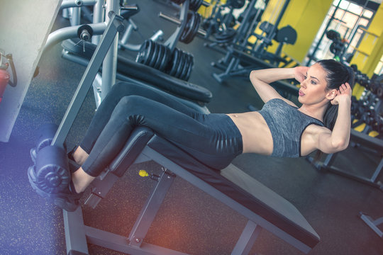 Fit girl doing push-ups on exercise machine in gym