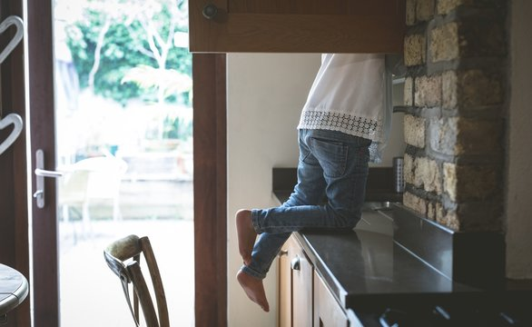 Girl searching for food in kitchen