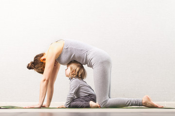 Foto auf Leinwand Gymnastik mother doing gymnastics yoga with baby. developing classes at home with a child. healthy lifestyle. Mom and baby doing physical culture