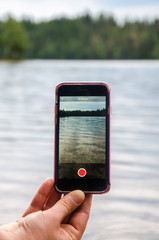 Hand holding smart phone while taking video in the nature