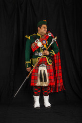 A portrait of an Indian American Scottish drum major smiling and looking away from camera in full Scottish regalia, including kilt and sporrans