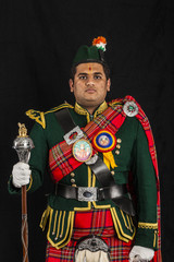 A portrait of an Indian American Scottish drum major looking at camera in full Scottish regalia, including kilt and sporrans