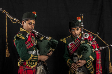 Two pipers of an Indian American Scottish bagpipe looking at camera in full Scottish regalia, including kilts and sporrans