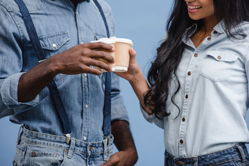 cropped image of african american couple clinking with coffee in paper cups isolated on blue