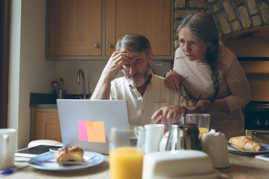 Senior couple using laptop on dining table