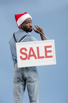 back view of handsome african american man in santa hat holding sale sign isolated on blue