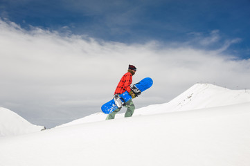 a guy rises to the snow-covered mountain, holding a blue snowboard against the sky