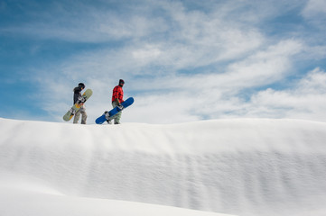 girl and guy in ski equipment with snowboards walking on a snow-covered road