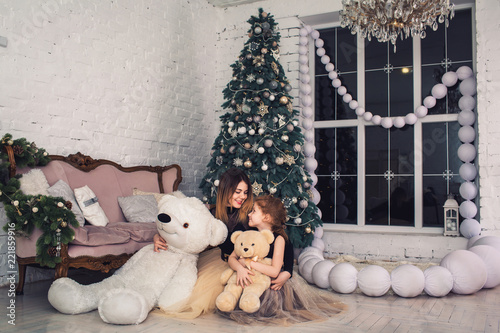 6b86999836 Happy mother and daughter are holding teddy bears on Christmas Eve ...