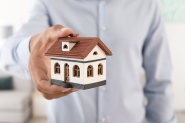 Real estate agent holding house model, closeup