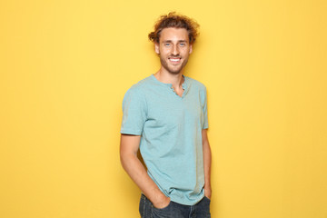 Young man in casual clothes posing on color background Fotoväggar