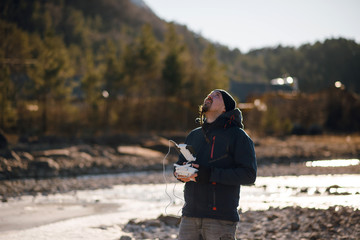 Young traveler man with beard in blue winter jacket operating drone with remote control. Scenic mountain view. Sunny winter day. Fjord, Norway