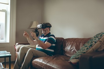 Senior man using virtual reality headset in living room