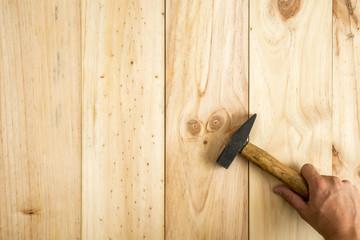 Mano de trabajador sujetando un martillo listo para trabajar sobre fondo de madera