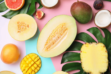 Flat lay composition with melon and other fruits on color background