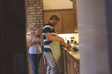 Senior couple cutting vegetable in kitchen