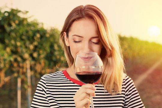 Young beautiful woman enjoying wine at vineyard on sunny day