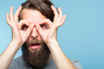 funny ludicrous joyful comic playful man pretending to look through binoculars made of hands. portrait of a young bearded guy on blue background. emotion facial expression concept Fototapete