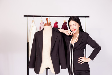 Happy smiling Asian female tailoring fashion designer with mannequin dummy and suit jackets in many colors on hanger.